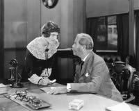 Donna con il pugno serrato in un ufficio che abbaglia al suo capo (tutte le persone rappresentate non sono vivente più lungo e ne immagini stock libere da diritti