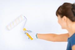 Donna con il rullo e la pittura che colorano la parete immagine stock