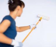 Donna con il rullo e la pittura che colorano la parete fotografia stock libera da diritti