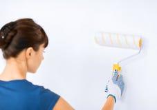 Donna con il rullo e la pittura che colorano la parete fotografia stock