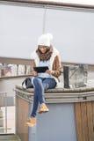 Donna con il sacchetto della spesa che esamina il computer della compressa nello stree Immagine Stock