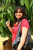 Donna con il sacchetto di mano di cuoio con l'albero dietro Fotografia Stock