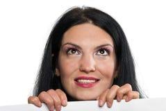 Donna con il segno che osserva in su Immagine Stock