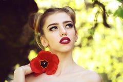 Donna con il seme di papavero rosso fotografia stock