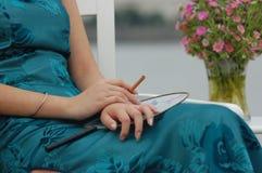 Donna con il sigaro ed i fiori Fotografie Stock