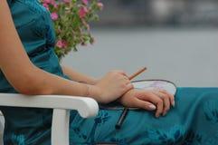 Donna con il sigaro ed i fiori Fotografia Stock