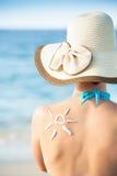 Donna con il sole ricavato da protezione solare sopra indietro Fotografie Stock Libere da Diritti
