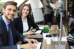 Donna con il suo personale, gruppo di affari della gente nel fondo all'ufficio luminoso moderno all'interno fotografia stock