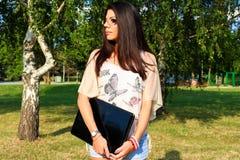 Donna con il taccuino in parco fotografie stock
