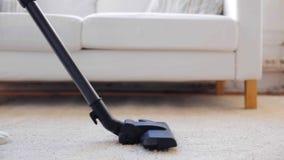Donna con il tappeto di pulizia dell'aspirapolvere a casa archivi video