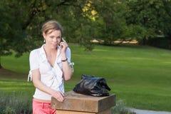Donna con il telefono astuto nella sosta Fotografia Stock