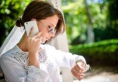 Donna con il telefono cellulare che esamina giù l'orologio Fotografia Stock