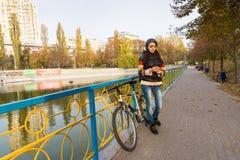 Donna con il telefono cellulare che si appoggia inferriata nel parco Fotografie Stock Libere da Diritti