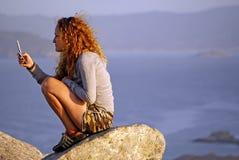 Donna con il telefono cellulare su una montagna nelle isole Spagna dei cies fotografie stock