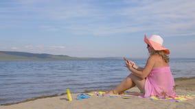 Donna con il telefono cellulare sulla spiaggia archivi video