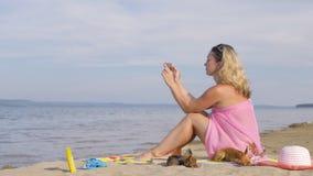 Donna con il telefono cellulare sulla spiaggia stock footage