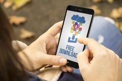 Donna con il telefono di download gratuito nel parco Fotografia Stock Libera da Diritti