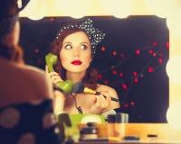 Donna con il telefono di quadrante che applica i cosmetici immagini stock