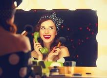 Donna con il telefono di quadrante che applica i cosmetici fotografia stock libera da diritti