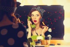 Donna con il telefono di quadrante che applica i cosmetici fotografia stock