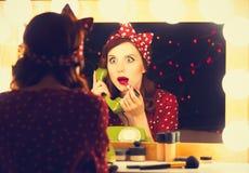 Donna con il telefono di quadrante che applica i cosmetici fotografie stock libere da diritti