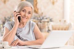 donna con il telefono facendo uso del computer portatile Immagini Stock Libere da Diritti