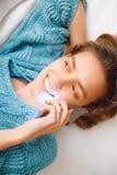 Donna con il telefono sul letto, sul sorriso e su felice fotografia stock