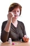 Donna con il termometro in una mano Fotografie Stock Libere da Diritti