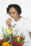 Donna con il tessuto della tenuta di allergia vicino ai fiori Fotografie Stock