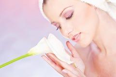Donna con il tovagliolo che tiene delicatamente fiore immagini stock
