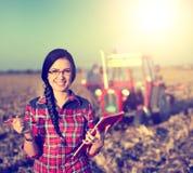Donna con il trattore sul campo Fotografie Stock