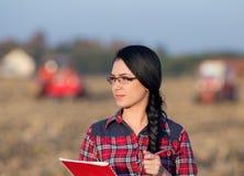 Donna con il trattore sul campo Fotografia Stock