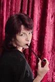 Donna con il tubo di tabacco Immagine Stock