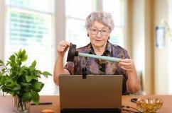 Donna con il tuffatore davanti al computer portatile fotografie stock libere da diritti
