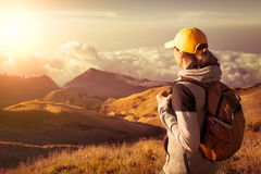 Donna con il viaggiatore con zaino e sacco a pelo che gode della vista in cima in alte montagne Fotografia Stock