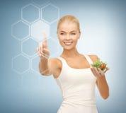 Donna con insalata e lo schermo virtuale Immagini Stock