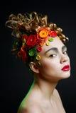 Donna con l'acconciatura di creatività con il butto colorato Immagini Stock