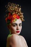 Donna con l'acconciatura di creatività con il tasto colorato Immagine Stock