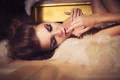 Donna con l'acconciatura riccia che mette su un pavimento vicino al letto di lusso Fotografie Stock