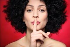 Donna con l'afro che fa gesto di silenzio Fotografie Stock