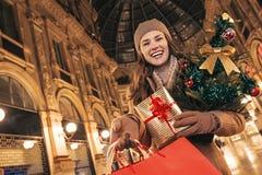 Donna con l'albero di Natale che mostra i sacchetti della spesa a Milano Fotografia Stock
