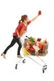 Donna con l'alimento di raccolto del carrello dall'alto armadietto Immagine Stock