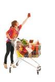Donna con l'alimento di raccolto del carrello dall'alto armadietto Immagini Stock Libere da Diritti