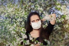 Donna con l'allergia con la maschera del respiratore nella decorazione di fioritura di primavera Immagine Stock Libera da Diritti