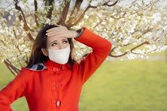 Donna con l'allergia con la maschera del respiratore nella decorazione di fioritura di primavera Fotografie Stock Libere da Diritti