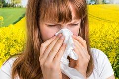 Donna con l'allergia sul campo giallo della violenza che starnutisce nel tessuto Fotografia Stock