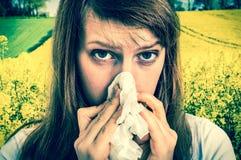 Donna con l'allergia sul campo giallo della violenza che starnutisce nel tessuto Fotografie Stock Libere da Diritti