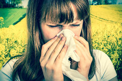 Donna con l'allergia sul campo giallo della violenza che starnutisce nel tessuto Fotografia Stock Libera da Diritti