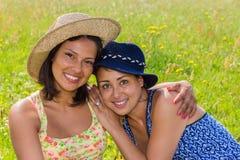 Donna con l'amico d'abbraccio del cappello in prato Fotografie Stock Libere da Diritti