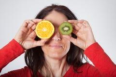 Donna con l'arancia ed il kiwi affettati sul suo occhio Fotografie Stock